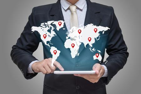 Businessman hand holding tablet global marketing on gray background Zdjęcie Seryjne