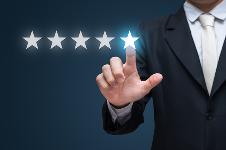 Businessman hand touch five stars on blue background