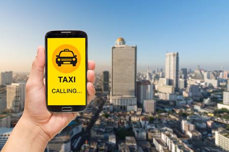 Une main tenant un téléphone intelligent sur la ville de fond Banque d'images - 61778799