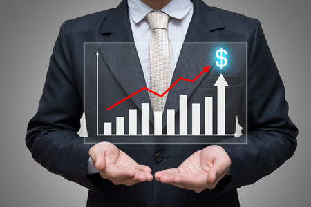 Businessman standing posture hand holding graph finance isolated on gray background 版權商用圖片
