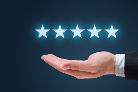Businessman hand holding five stars isolated on blue background 版權商用圖片