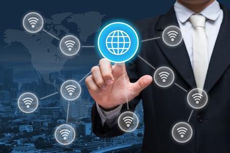 Businessman hand touch social network wifi symbol on city background Zdjęcie Seryjne