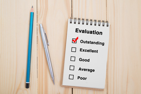 Performance evaluation check box on notebook with pen and pencil