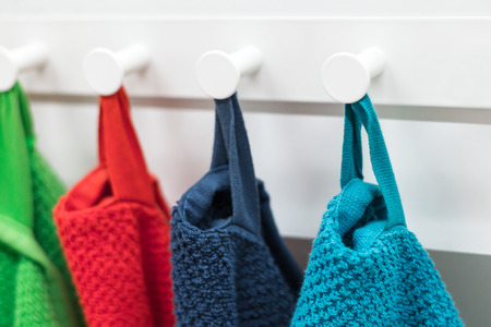 Colored towels hanging on the rack in the kitchen