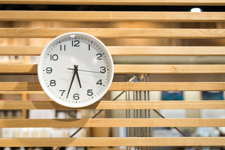 White clock on wooden wall