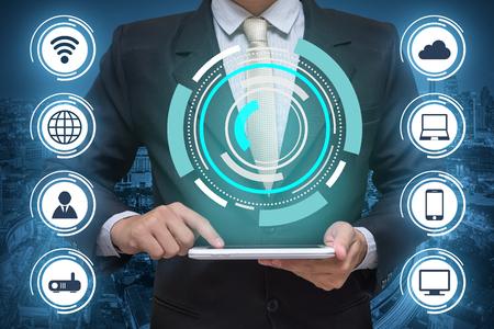 Homme d'affaires tenant une tablette PC et réseau de communication sans fil sur fond de ville Banque d'images - 74114646