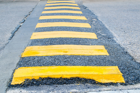 A yellow stripe speed ramp on an asphalt road Фото со стока