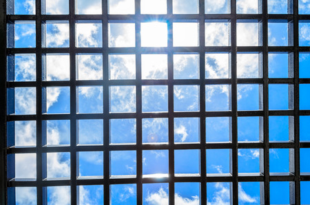 metal grate: Steel rectangular mesh panel overlooking the blue sky day with sunshine