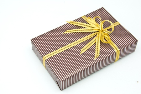 Black gift box with white bar attached gold ribbon on white background. Stock Photo - 8561429