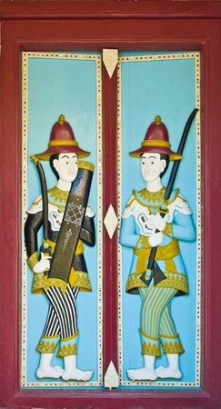 painted carved wood in temple door decorated ,thai style in temple at Watphrakaew, Bangkok, Thailand photo