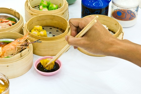 Hand holding chopsticks reaching out for Dim Sum food in restaurant. photo