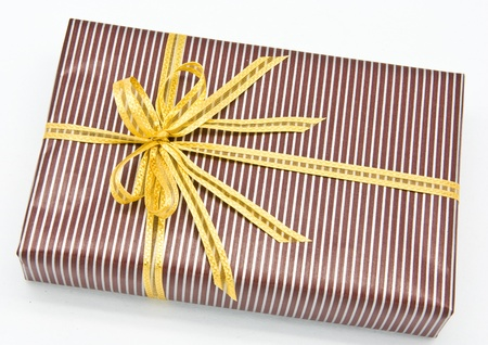 Black gift box with white bar attached gold ribbon on white background. Stock Photo - 9240782