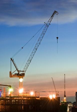 Derrick grues au chantier de construction au moment du coucher du soleil
