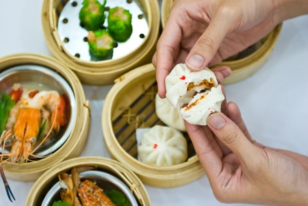 Steamed dumpling and dimsum with hand photo