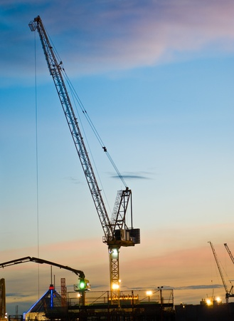 Derrick cranes at construction site at sunset time photo
