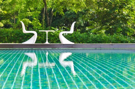 Two white deck chairs side swimming pool. photo