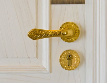 door knob: golden door handle and deadbolt on wooden door Stock Photo