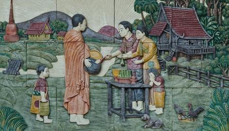 moine: stuc culture d'origine thaïlandaise sur le mur du temple, Thaïlande, donner des offrandes de nourriture à un moine bouddhiste