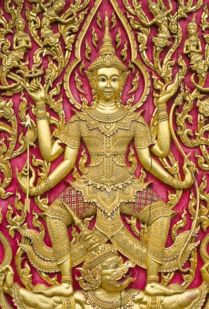 seraph wood carved gold paint on temple door, Thailand