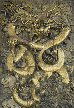 stucco golden dragon on the temple wall, Thailand Editorial