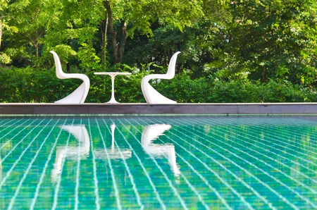 Two white deck chairs side swimming pool.