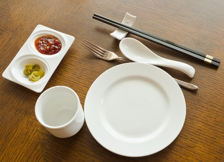 view of dinner place setting. A white plate with stainless fork and cup and chopsticks on the  wood table photo