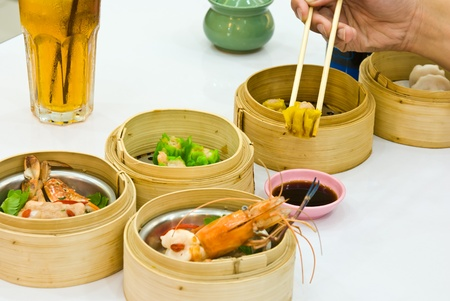 Hand holding chopsticks reaching out for Dim Sum food in restaurant  photo