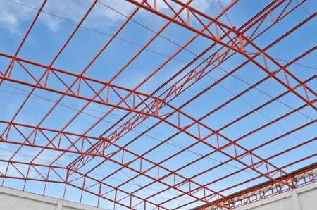 steel blue: Steel roof trusses sitting on concrete pole view from inside home factory. Blue sky with clouds in background.