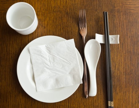 view of dinner place setting  A white plate with stainless fork and cup and chopsticks on the  wood table photo