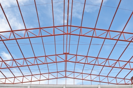 Steel roof trusses sitting on concrete pole view from inside home factory. Blue sky with clouds in background.