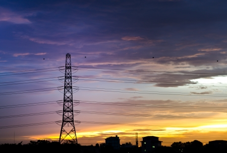 electricity pylon in the  city  silhouetted against at  the sunset photo