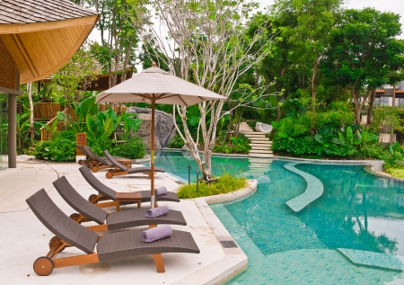 Beach chairs and umbrella side swimming pool at Phuket, Thailand