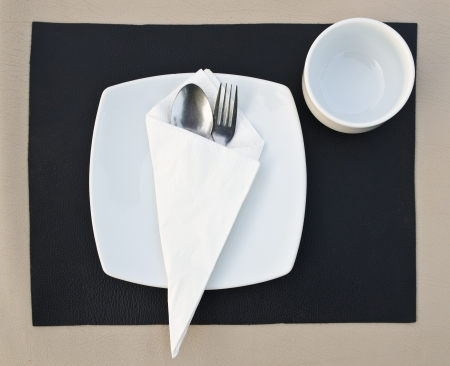 Dinner place setting. A white plate with stainless fork and cup photo