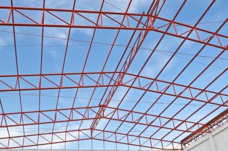 acier: Fermes de toit en acier assis sur poteau en b�ton vue de l'int�rieur de l'usine � la maison. Ciel bleu avec des nuages ??en arri�re-plan. Banque d'images