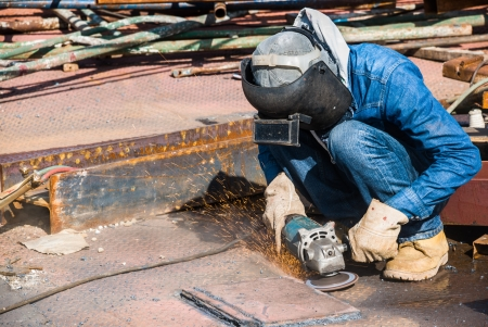 professional worker in construction industry grinding metal on a steel floor Stock Photo - 16030204