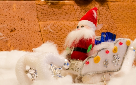 doll of Santa Claus sitting on car  in snow photo