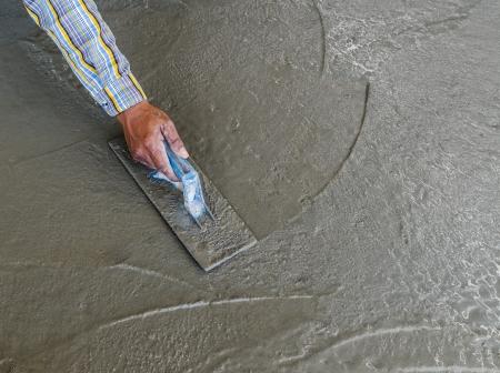 こてを使用してぬれたコンクリート床を完了する手のクローズ アップ
