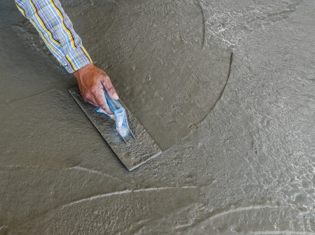 Close-up of hand using trowel to finish wet concrete floor photo