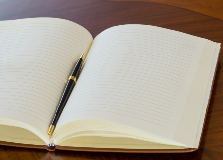Open notepad and pen  on wood table background. photo