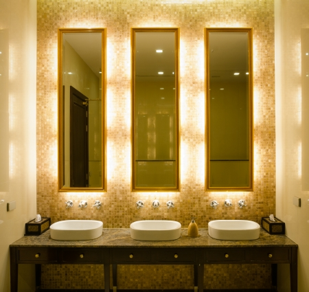 View Modern style interior design of a bathroom. Install bulb behind a mirror glass decorative gold picture frame and faucet and wash bowl on table
