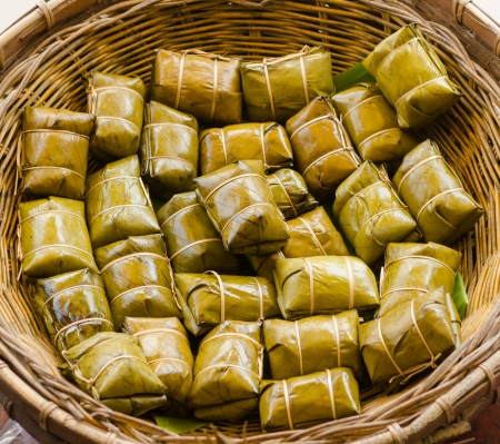 Traditional Thai food style, Glutinous rice steamed in banana leaf ( Khao Tom Mat or Khao Tom Pad ) bananas and sticky rice inside on wicker basket in culture market at Thailand photo