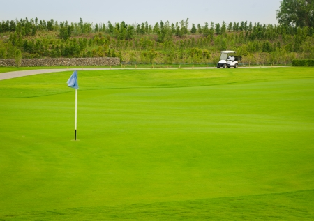 Sport view landscape green grass pattern and golf cart and blue flag of golf course at Thailand photo