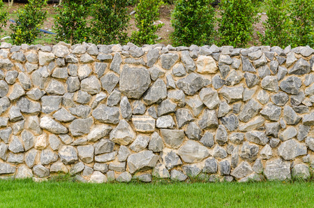 background pattern gray color of modern style design decorative fence real stone wall surface with cement on green grass field Stock Photo