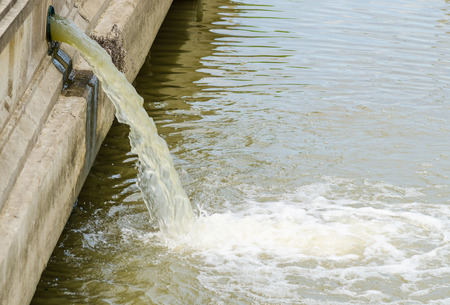 Photo of flow out water from the conduit of Industrial factory to the river photo