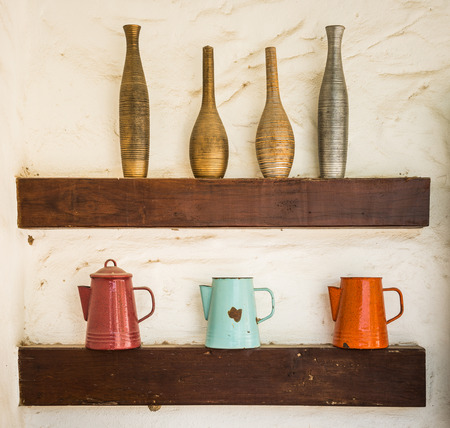 vintage style colorful vase baked clay and steel jug put on wood shelf at white wall background photo
