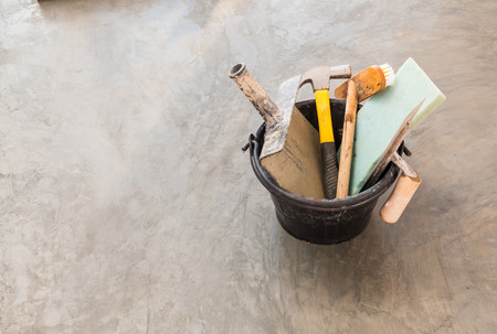 close up construction tools for concrete job in black plastic bucket on background of polished concrete surface