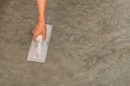 polished floor: Close up of hand using steel trowel to finish wet concrete floor of polished concrete surface