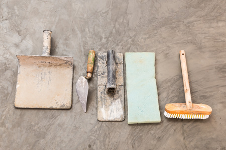 close up construction tools for concrete job on background of polished concrete surface photo