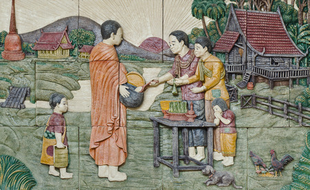 native culture Thai stucco on the temple wall,  Thailand, give food offerings to a Buddhist monk