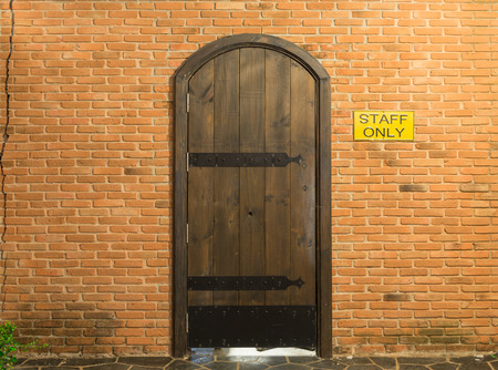 staff only: Wood arch door on red brick wall background for staff only